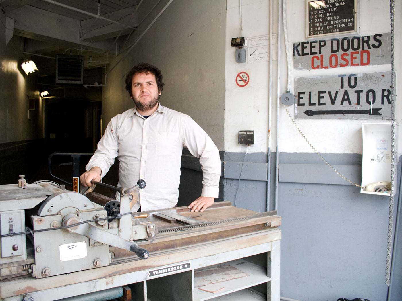 Ryan in front of a Vandercook printing press on a loading dock of our old shop.
