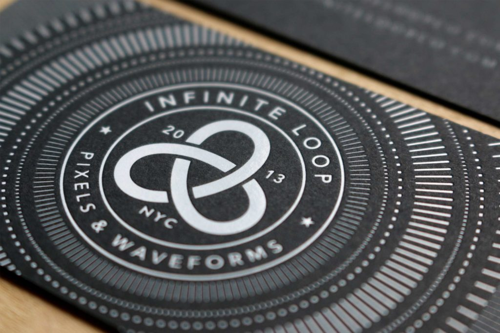 white foil on black paper business card